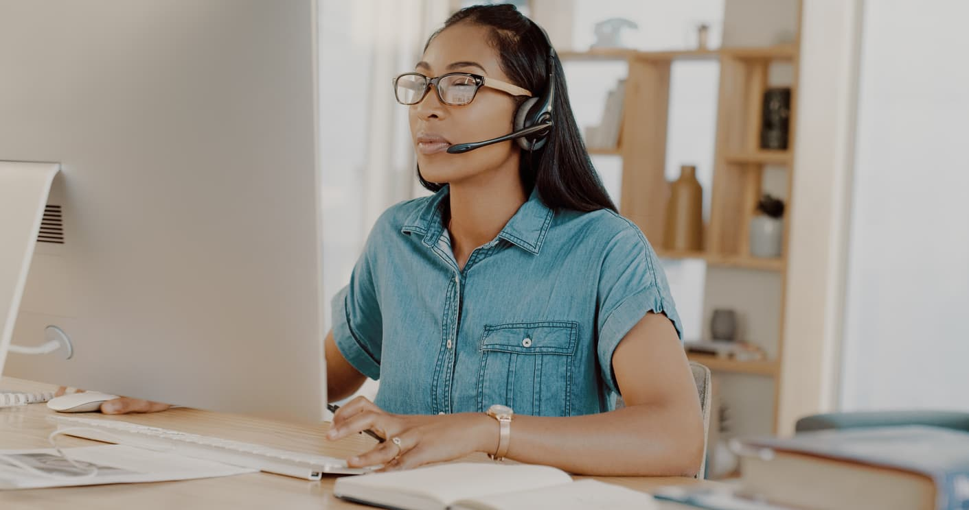 young businesswoman wearing headsets and working on a computer at home